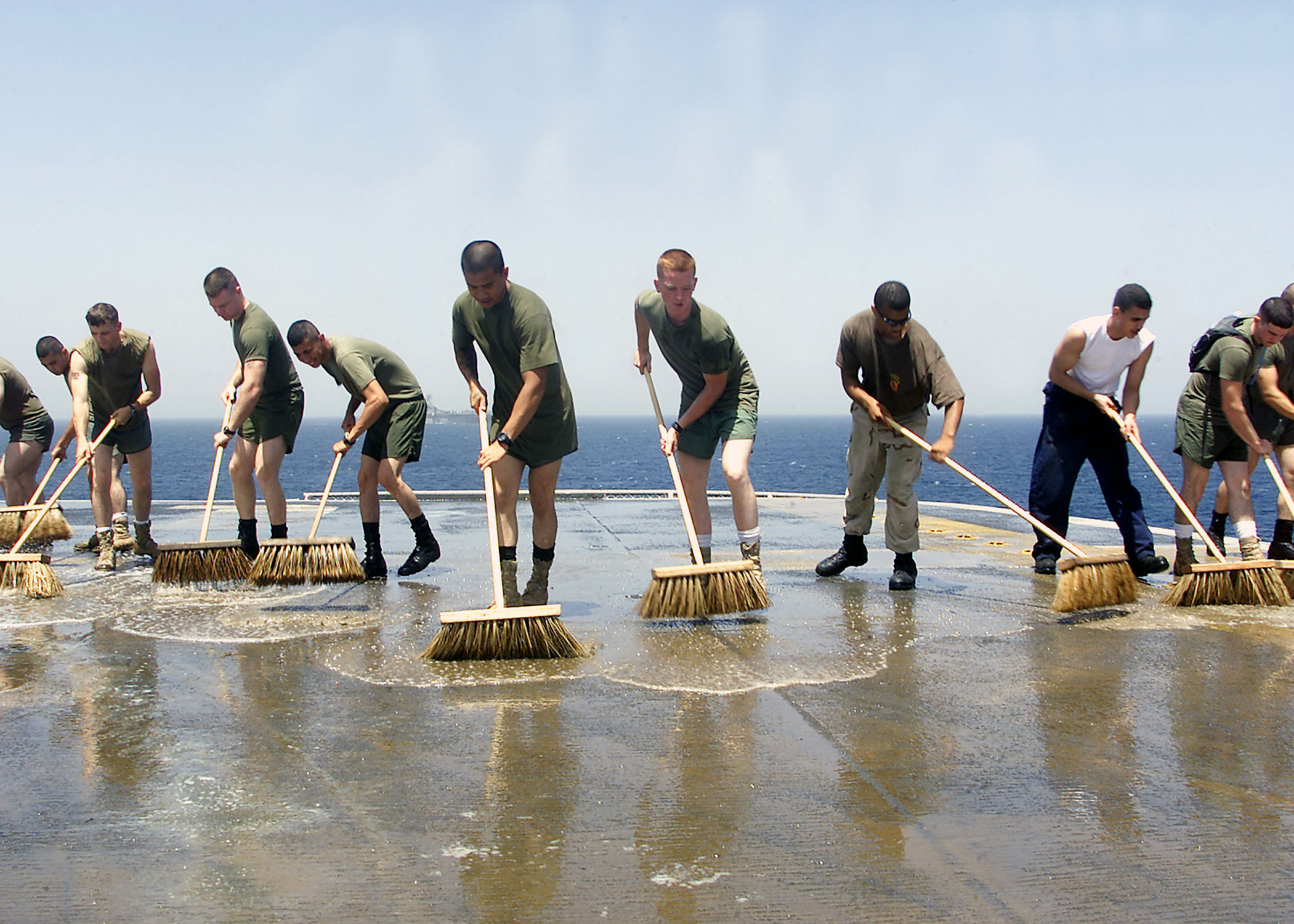 US_Navy_030521-N-9109V-003_Sailors_and_embarked_Marines_flood_the_flight_deck_with_salt-water_solution,_scrub_brooms,_and_plenty_of_elbow_grease_in_a_mandatory_wash_down.jpg
